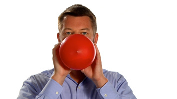 Man blowing up a red balloon in front of a white backdrop