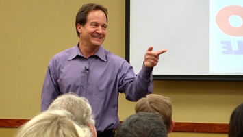 Jim Link pointing to a person in the crowd during a presentation