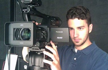 Photo of Ryan operating a digital video camera.
