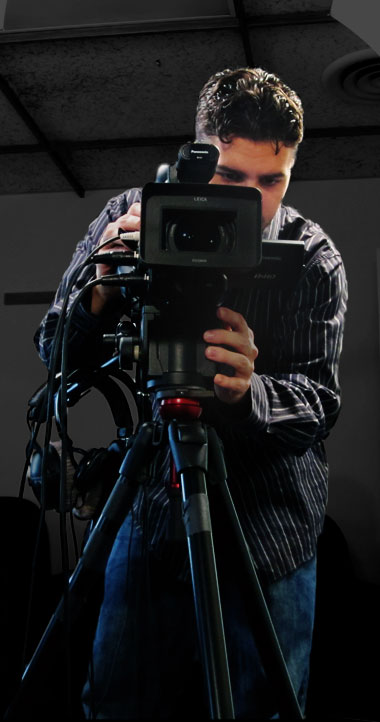 Full body photo of Ryan operating a digital video camera mounted on a tripod.